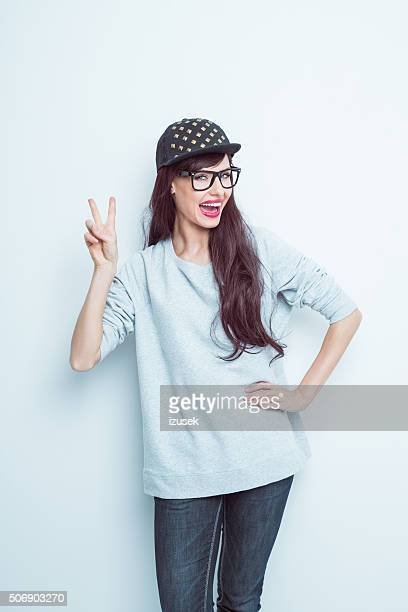 Excited long hair brunette in casual outfit showing V sign