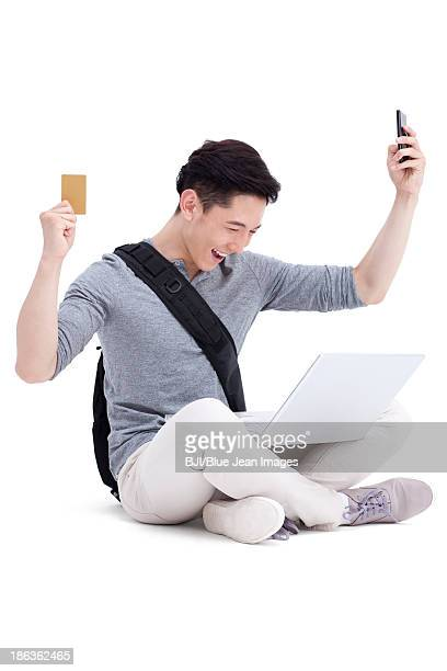Excited male college student shopping online