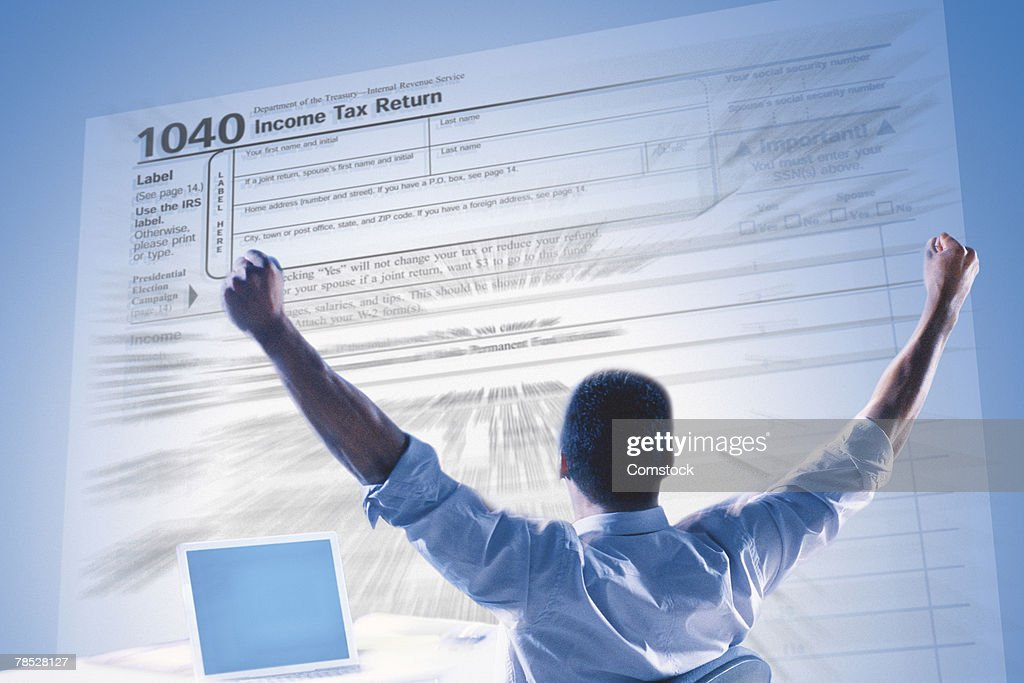 Excited man and income tax form : Stock-Foto