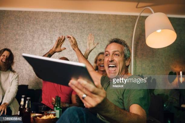 excited man cheering with digital tablet while watching sports at home - watch what happens: live stock pictures, royalty-free photos & images
