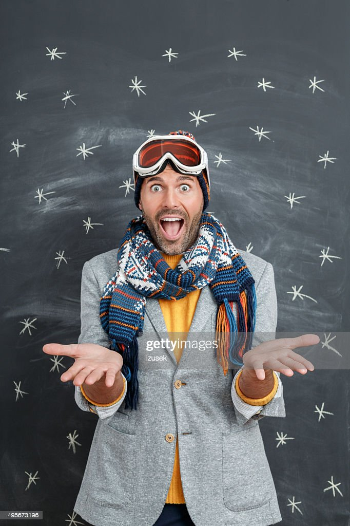 Excited man in winter outfit against blackboard : Stock Photo