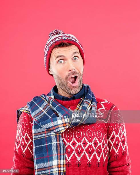 Excitación hombre en invierno negocio contra fondo rojo