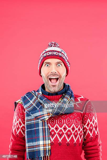 Excited man in winter outfit against red background