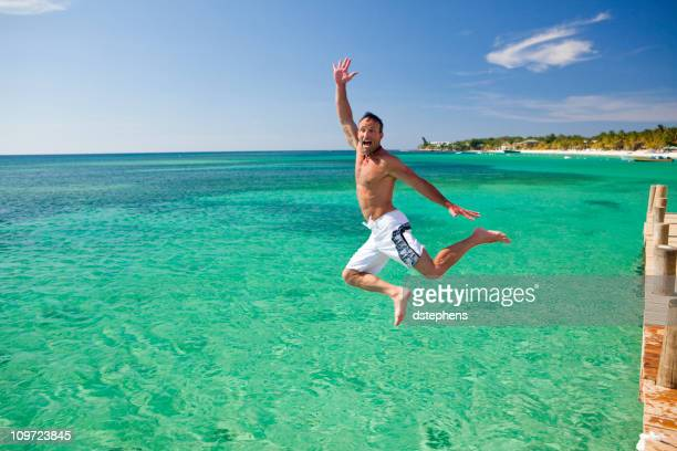 Excited man jumping into Caribbean Sea