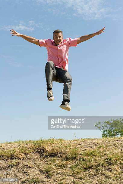 Excited man jumping into the air with arms raised