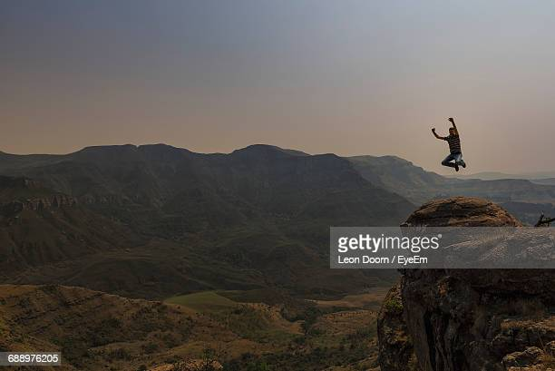 Excited Man Jumping Over Rock Formation Against Sky