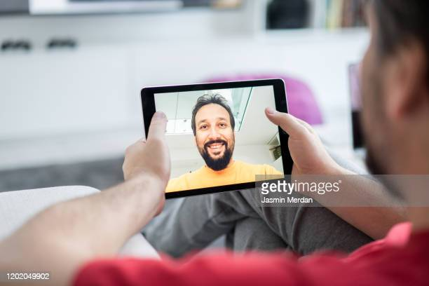 excited man making a video call at home - conference call stock pictures, royalty-free photos & images