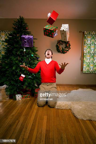 Excited man on Christmas morning with gifts falling
