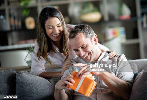 excited man opening a present for their anniversary that his partner just gave him - anniversary stock pictures, royalty-free photos & images