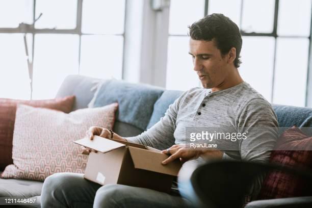 excited man opens package delivery - descoberta imagens e fotografias de stock
