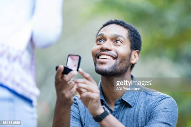 excited man proposes to girlfriend - fiancé stock pictures, royalty-free photos & images