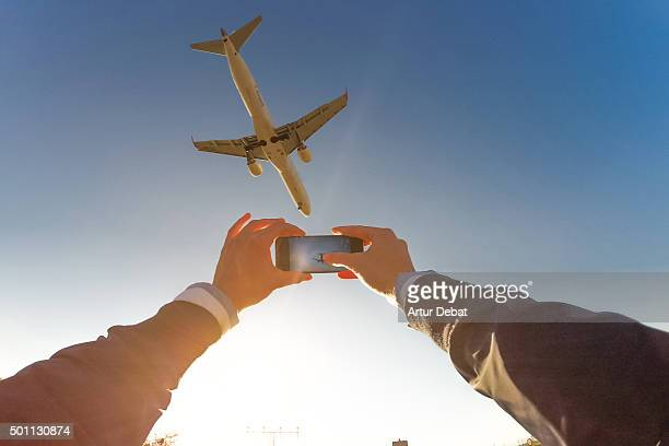 Excited man raising arms taking pictures from personal point of view with airplane overhead.
