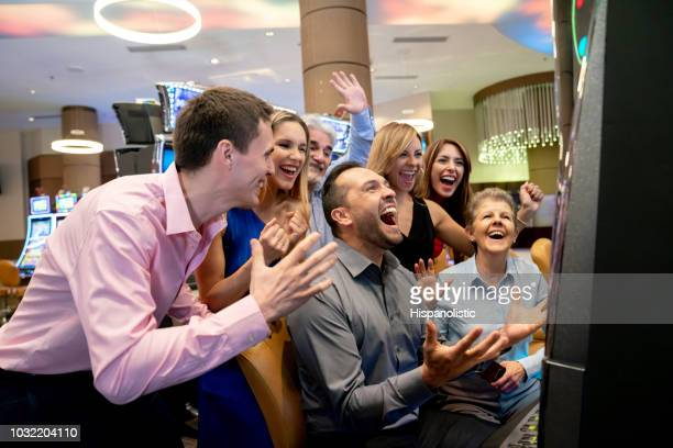 excited man shouting because he just won the jackpot on slot machines and everyone around him celebrating - jackpot stock pictures, royalty-free photos & images