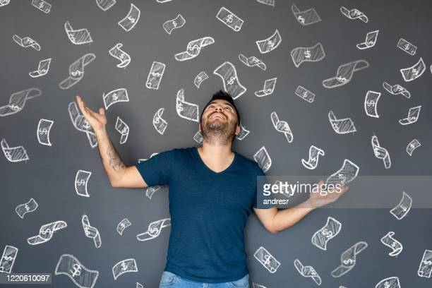 excited man under a shower of money - lottery stock pictures, royalty-free photos & images