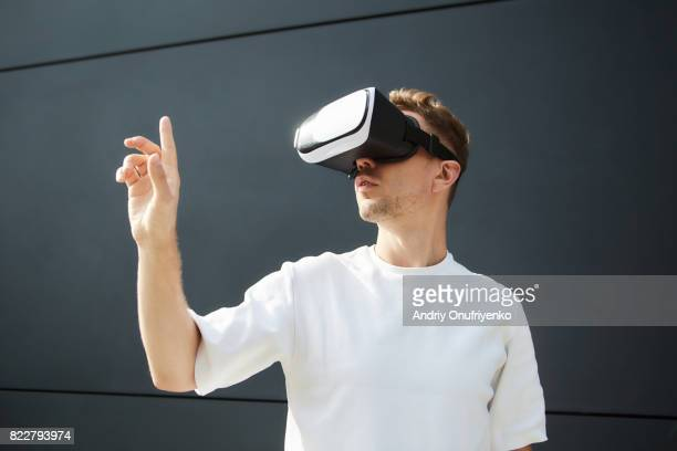 excited man wearing vr glasses outdoors - simulatore di realtà virtuale foto e immagini stock
