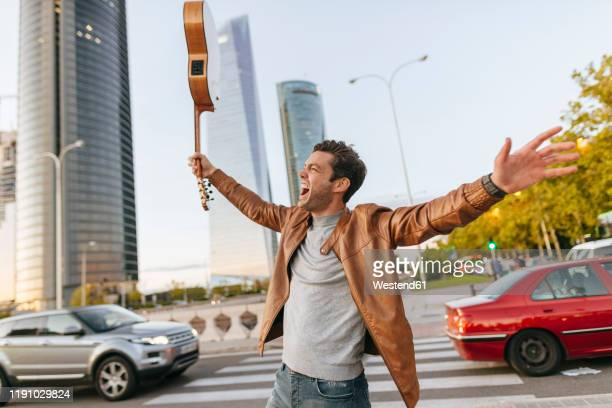 excited man with guitar in the city, madrid, spain - レザージャケット ストックフォトと画像