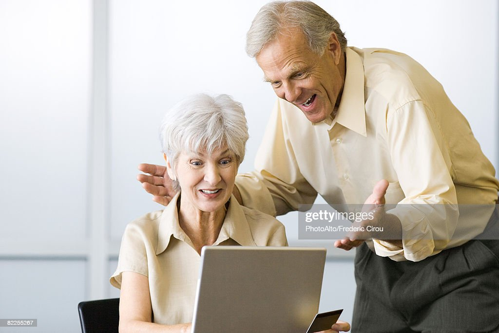 Excited mature couple looking at laptop computer together, woman holding credit card : Stock Photo
