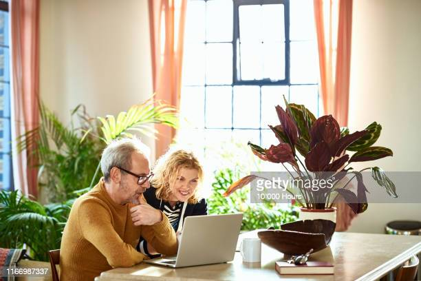 excited mature woman looking at laptop with her husband - planning stock pictures, royalty-free photos & images