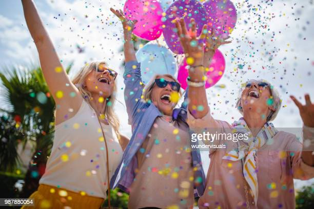 Excited mature women celebrating with colorful confetti and balloons outdoors