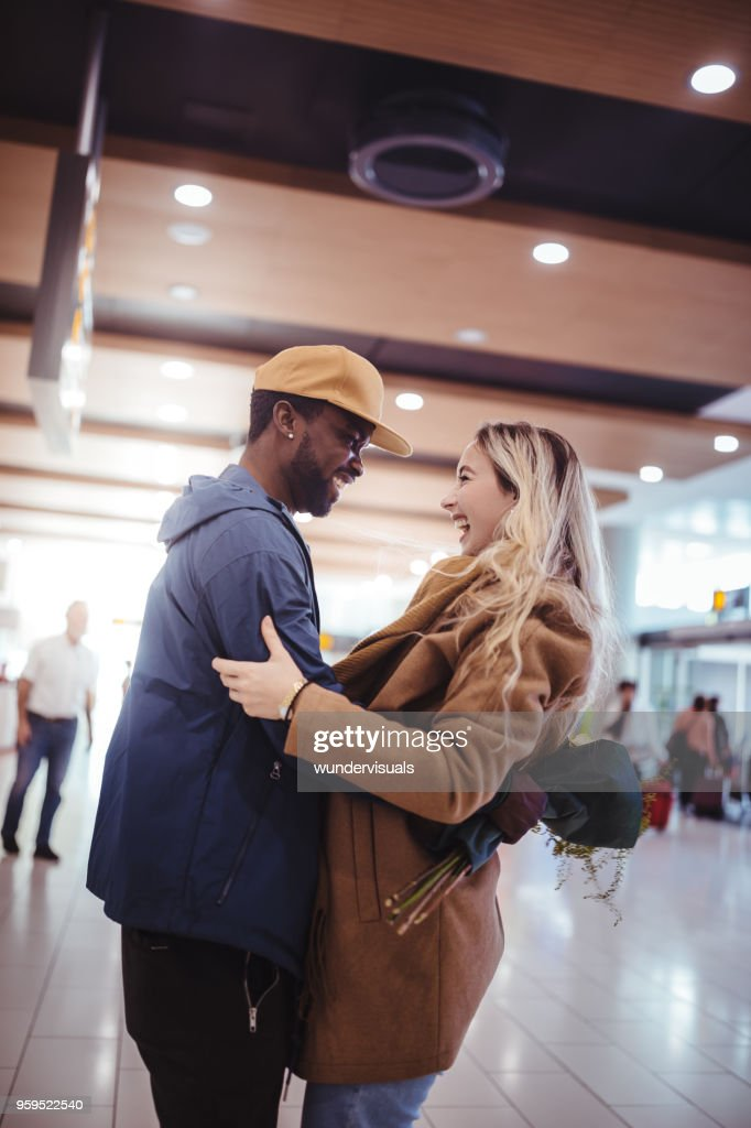 Excited multi-ethnic friends meeting at airport after flight arrival : Stock Photo