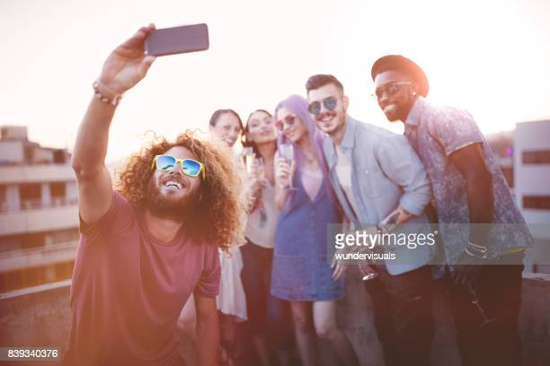 Excited multi-ethnic hipster friends taking a selfie at rooftop party