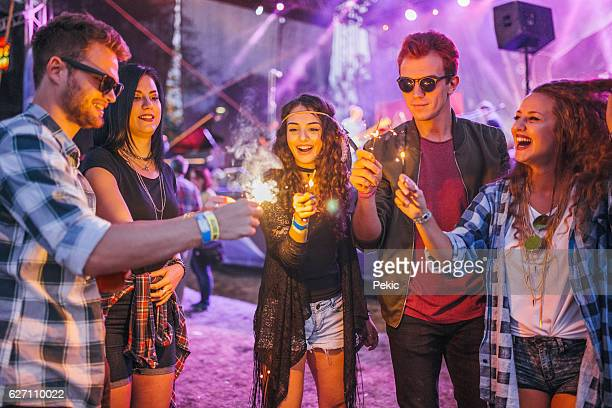 excited music fans with sparklers at music festival - bevrijding stockfoto's en -beelden