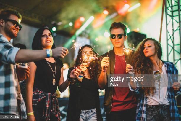 Opgewonden muziekliefhebbers met wonderkaarsen op muziekfestival
