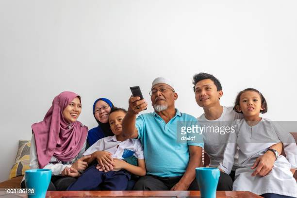 excited muslim three generation asian family watching tv together - malay stock photos and pictures