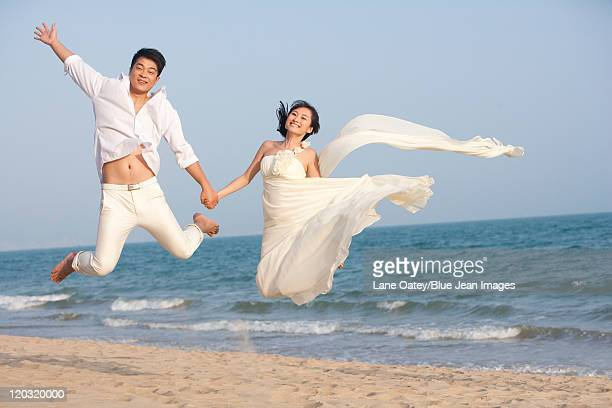 Excited Newlyweds Jumping Up