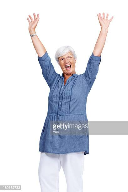 Excited old woman standing with her arms raised