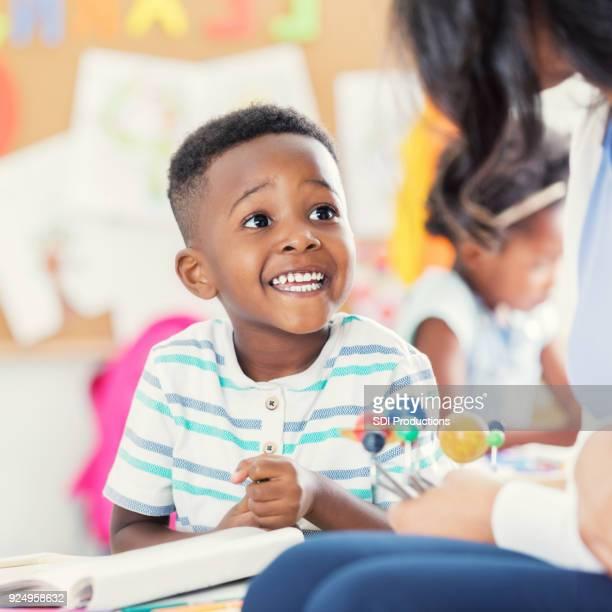 Excited preschool age boy studies solar system model with teacher
