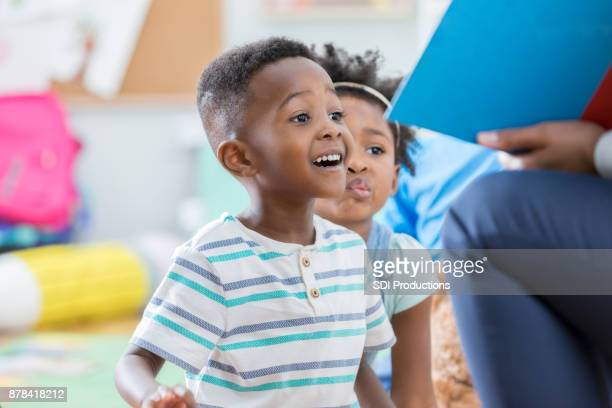 excited preschool boy enjoying story time - preschool age stock pictures, royalty-free photos & images