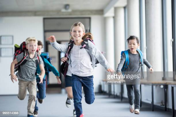 excited pupils rushing down school corridor - schulgebäude stock-fotos und bilder