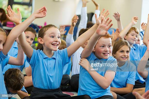 excited school children in uniform with hands up - schoolkinderen stockfoto's en -beelden