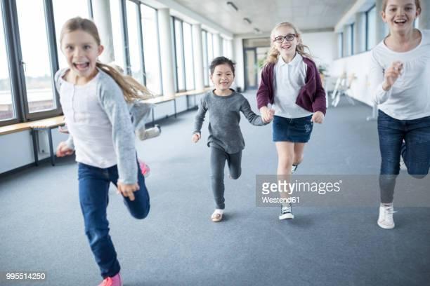 excited schoolgirls rushing down school corridor - schulkind nur mädchen stock-fotos und bilder