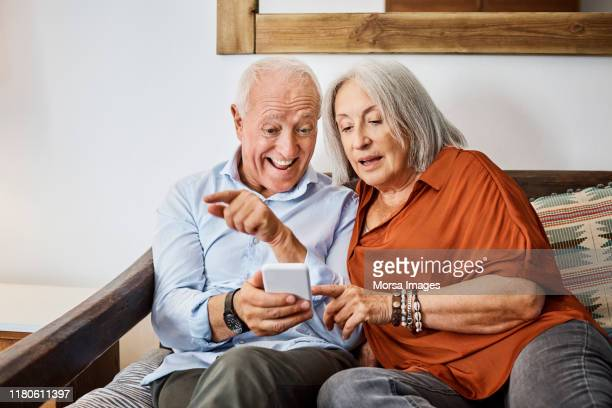 excited senior couple looking at smart phone in house - excitement stock pictures, royalty-free photos & images