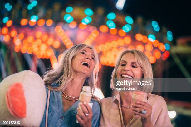 excited senior friends eating ice cream on funfair night out - carefree stock pictures, royalty-free photos & images