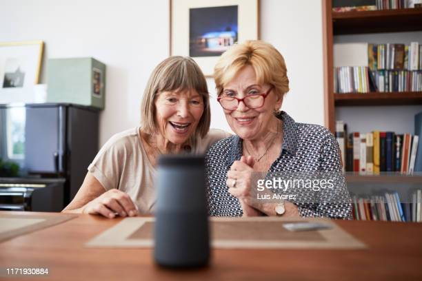 excited senior friends using a smart speaker - arts culture and entertainment stock pictures, royalty-free photos & images