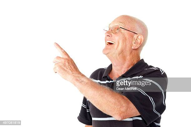 Excited senior man pointing at copyspace