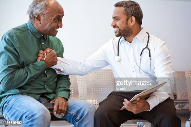 excited senior man shaking hands with doctor - outpatient care stock pictures, royalty-free photos & images