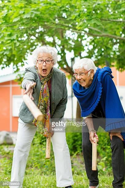 Excited senior people enjoying kubb game at park