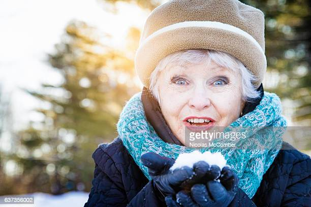 Excited senior woman portrait lifting handful of snow and smiling