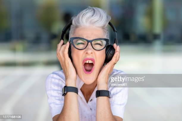 excited senior woman screaming while listening to music through headphones - listening stock pictures, royalty-free photos & images