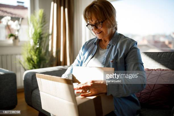 excited senior woman unpacking online order - unboxing stock pictures, royalty-free photos & images