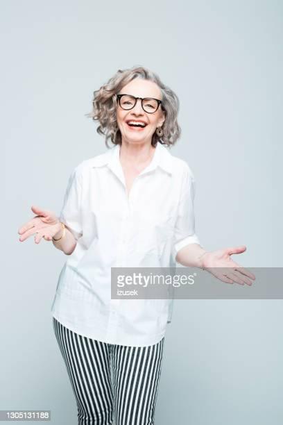 opgewekte hogere vrouw die overhemd en gestreepte broek draagt - izusek stockfoto's en -beelden