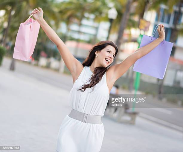 excited shopping woman holding bags with arms open - female armpits stock pictures, royalty-free photos & images