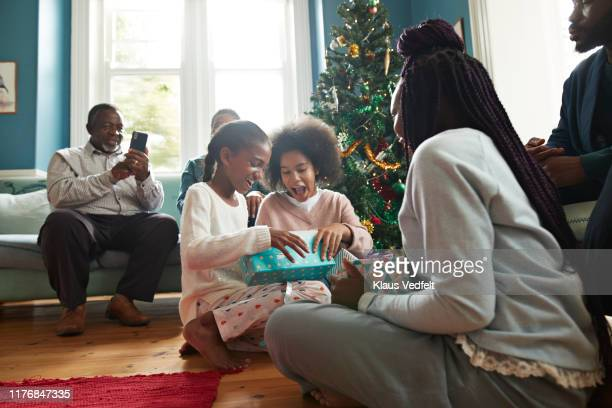 excited sisters opening christmas presents at home - holiday stock pictures, royalty-free photos & images