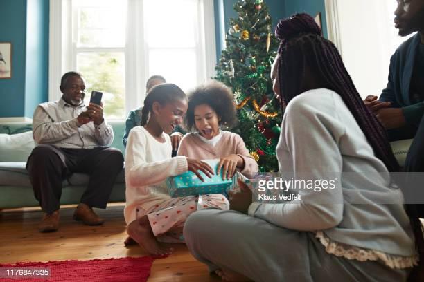 excited sisters opening christmas presents at home - presente de natal - fotografias e filmes do acervo