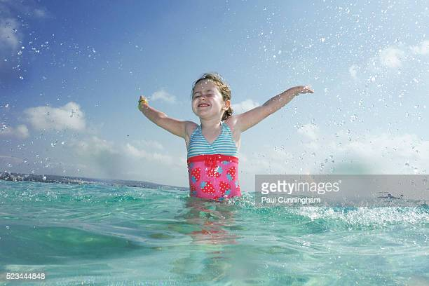 Excited smiling child leaps from the ocean.