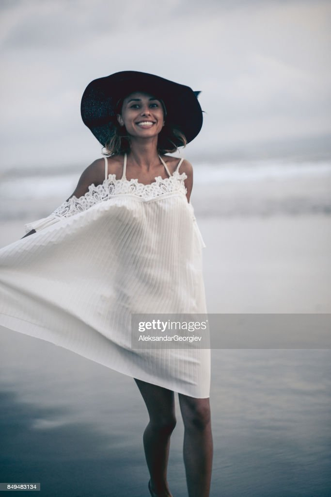 Excited Smiling Female Walking At The Beach In Wet Dress Stock Photo